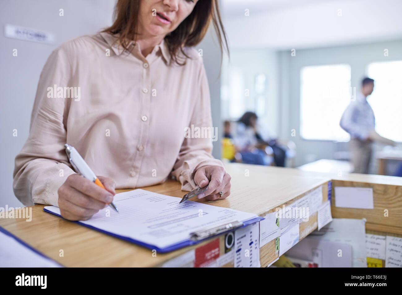 Frau mit Kreditkarte ausfüllen Krankenversicherung Schreibarbeit in Klinik Stockbild