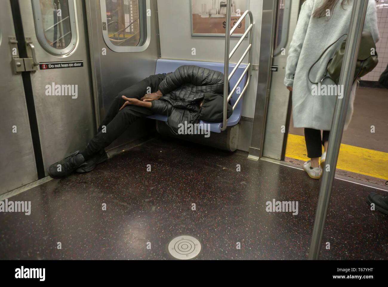 Eine obdachlose Person gesehen wird, schlafen auf einem Sitz in der U-Bahn in New York am Donnerstag, 18. April 2019. (© Richard B. Levine) Stockbild