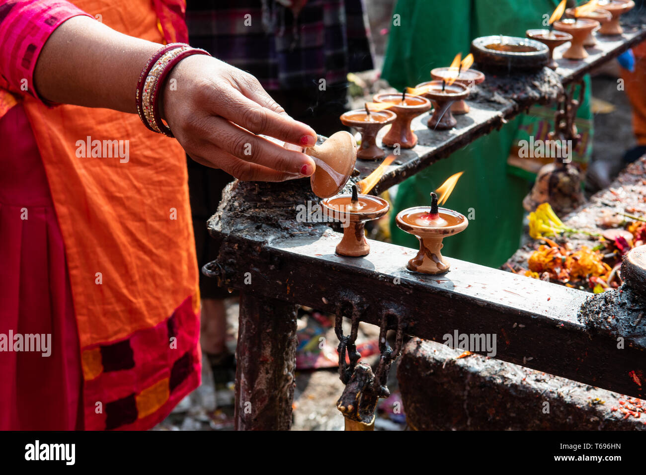 Hand der weiblichen 20 bis 30 Jahre alten nepalesischen Hindu devotee mit Öllampen in Kathmandu, Nepal. Stockbild