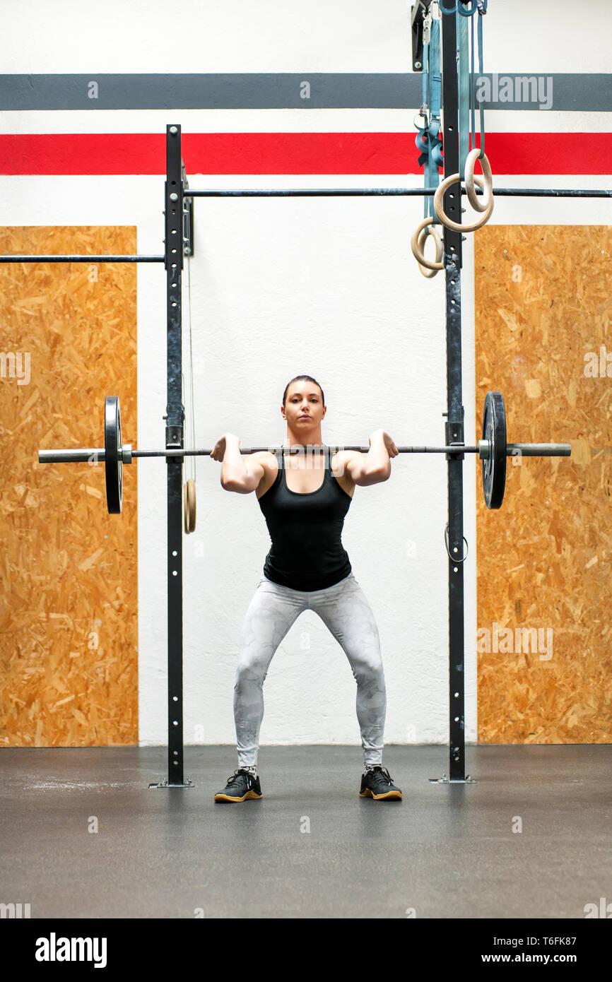 Junge Frau Body Builder oder Athlet eine front Squat in einer Turnhalle heben die Langhantel auf den Schultern in der aufrechten Position Ihr Muskel zu stärken Stockbild