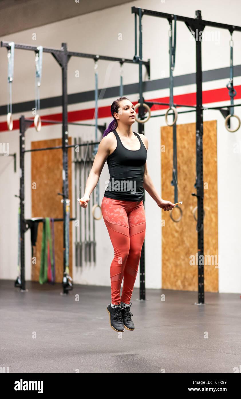 Junge Frau, die das Arbeiten mit einem Springseil in einem professionellen Fitnessraum in voller Länge ansehen in einem Gesundheit und Fitness Concept Stockbild