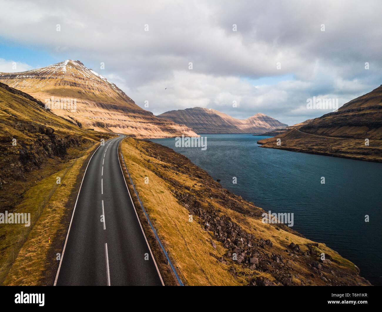 Luftaufnahme von einer Küstenstrasse entlang einer Färöischen Fjord mit atemberaubenden Bergketten, dramatischer Himmel und türkisfarbenem Wasser (Färöer, Dänemark, Europa) Stockfoto