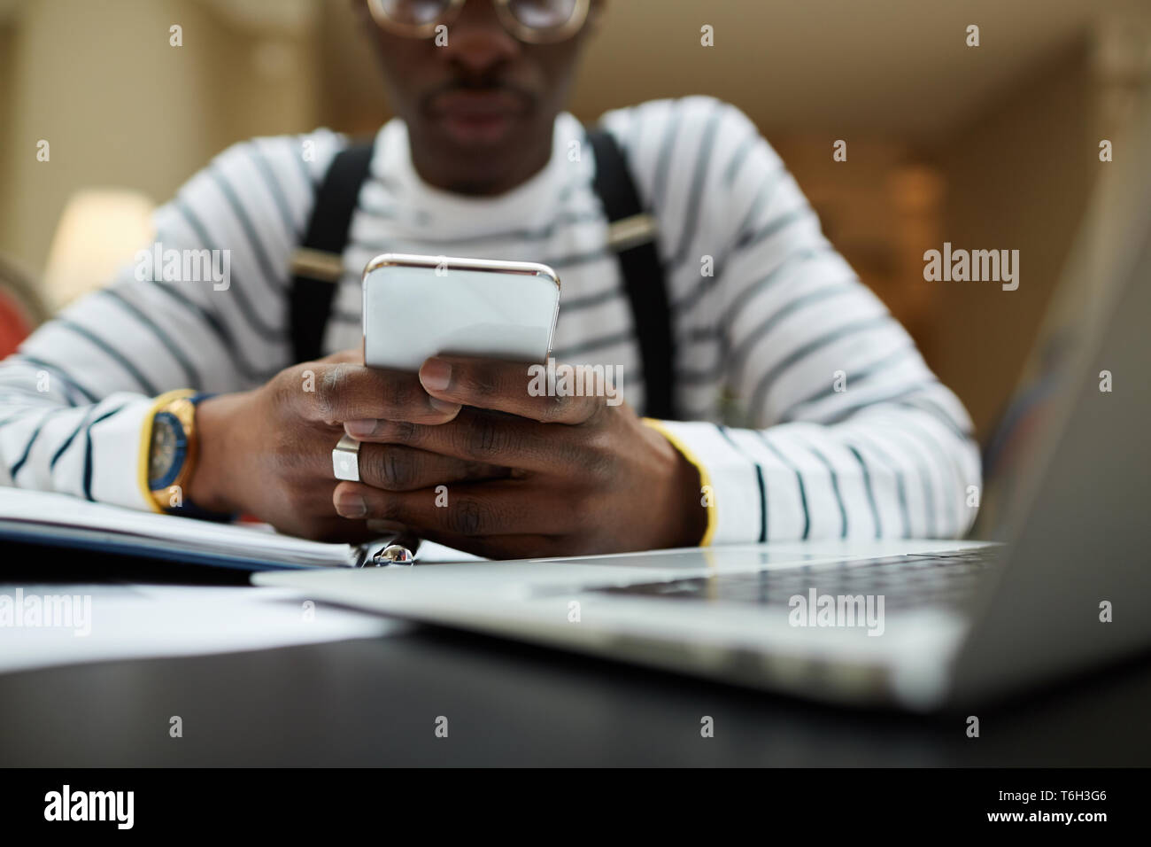 Nahaufnahme der zeitgenössischen afrikanischen Kursteilnehmer sie ihr Smartphone während des Studiums in Bibliothek, Raum kopieren Stockbild