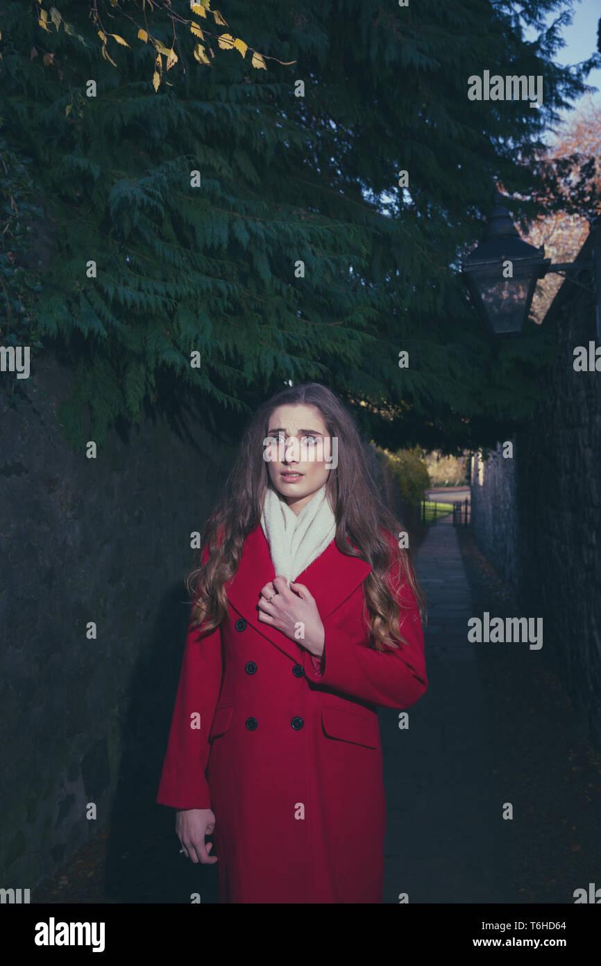 Verängstigte Frau in einer dunklen Gasse, die alle allein ist Stockfoto