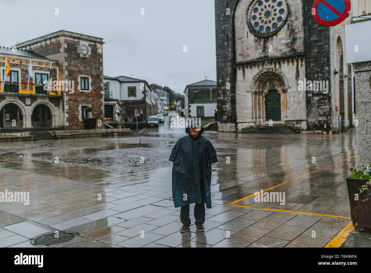 Gerne älterer Mann Portrait mit einem regenmantel auf, vor einer romanischen Kirche während der Jakobsweg. Stockbild