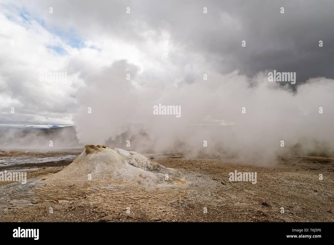 Vulkanische Landschaft mit einer großen Fumarole, die eine Menge Dampf löst, im Hintergrund weiter Dampf, Wind lässt den Dampf in der Horizontalen Stockbild