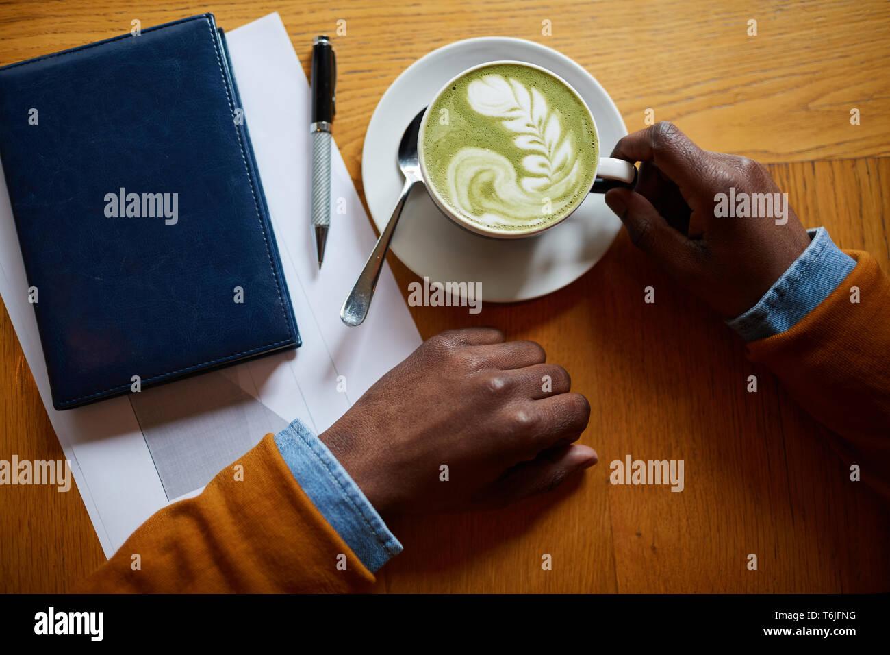 Ansicht von oben Nahaufnahme des zeitgenössischen afroamerikanischen Mann trinken Latte beim Sitzen am Tisch im Coffee Shop, kopieren Raum Stockbild