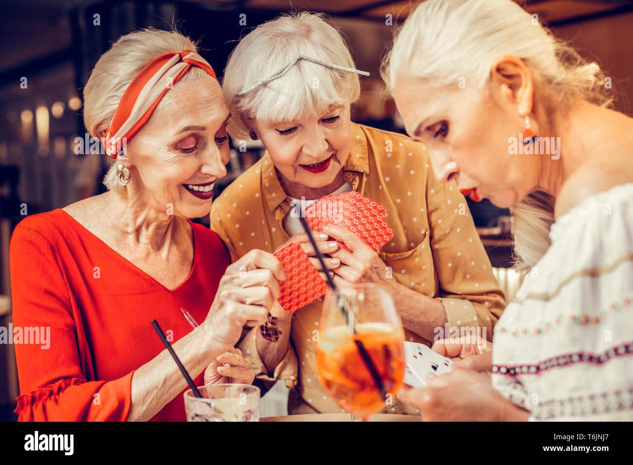 Cheaten Lächeln ältere Frau heimlich ihre Karten Stockbild