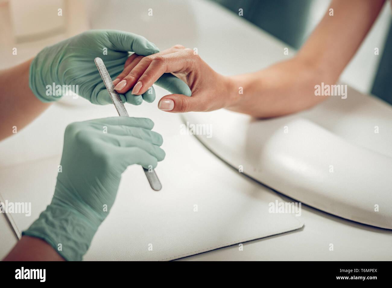 Professionell ausgebildete Nail master durch das Tragen von schützender Gummihandschuhe Stockbild