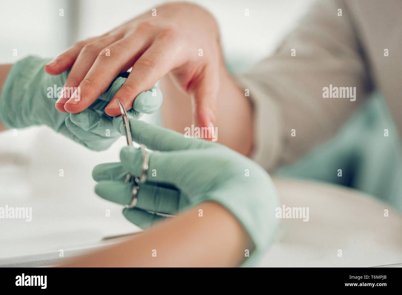 Präzise qualifizierten Nagel Master in Gummischutzhandschuhe schneiden extra Haut Stockbild