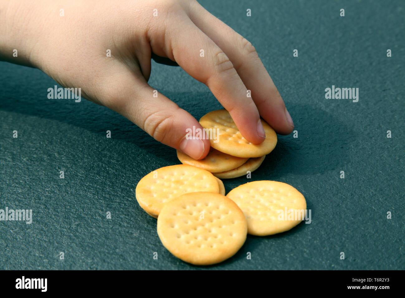 Die Hand des Kindes, die Jacobs Mini Cheddars aus schwarzem Schiefer Hintergrund Stockbild