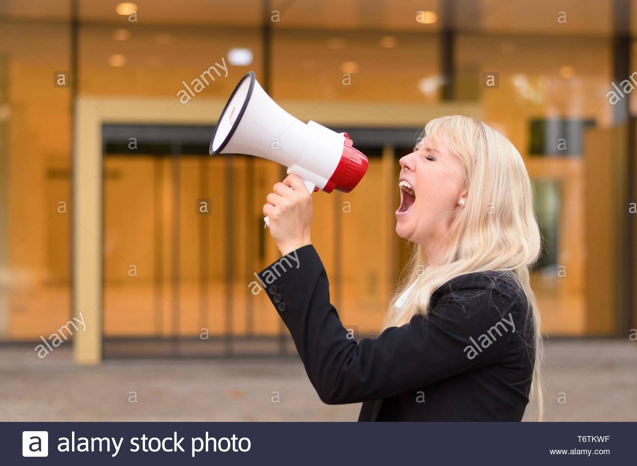 Wütende Frau Demonstrant in ein Megaphon brüllt Stockbild