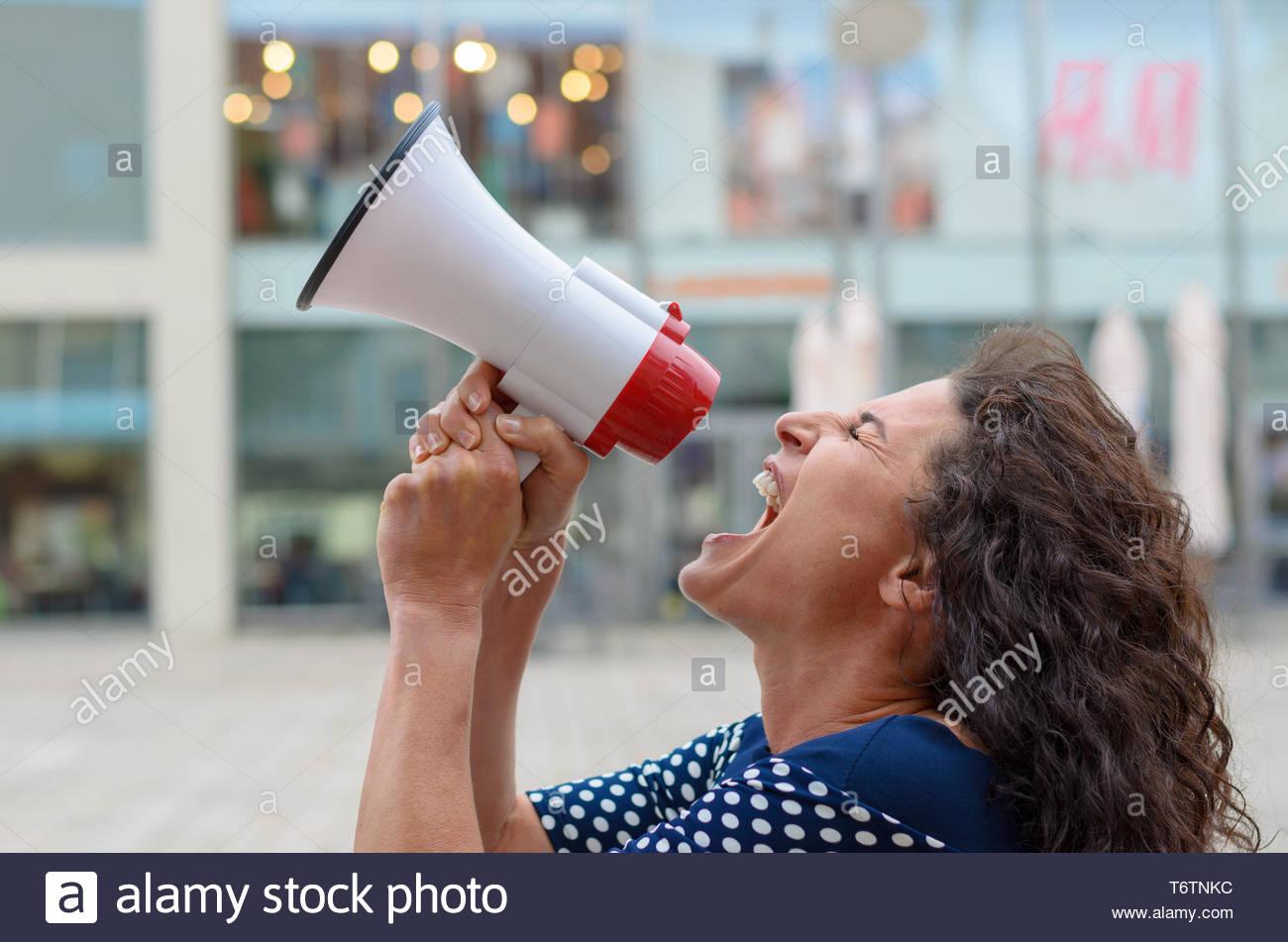Junge Frau Demonstrant in ein Megaphon riefen Stockbild
