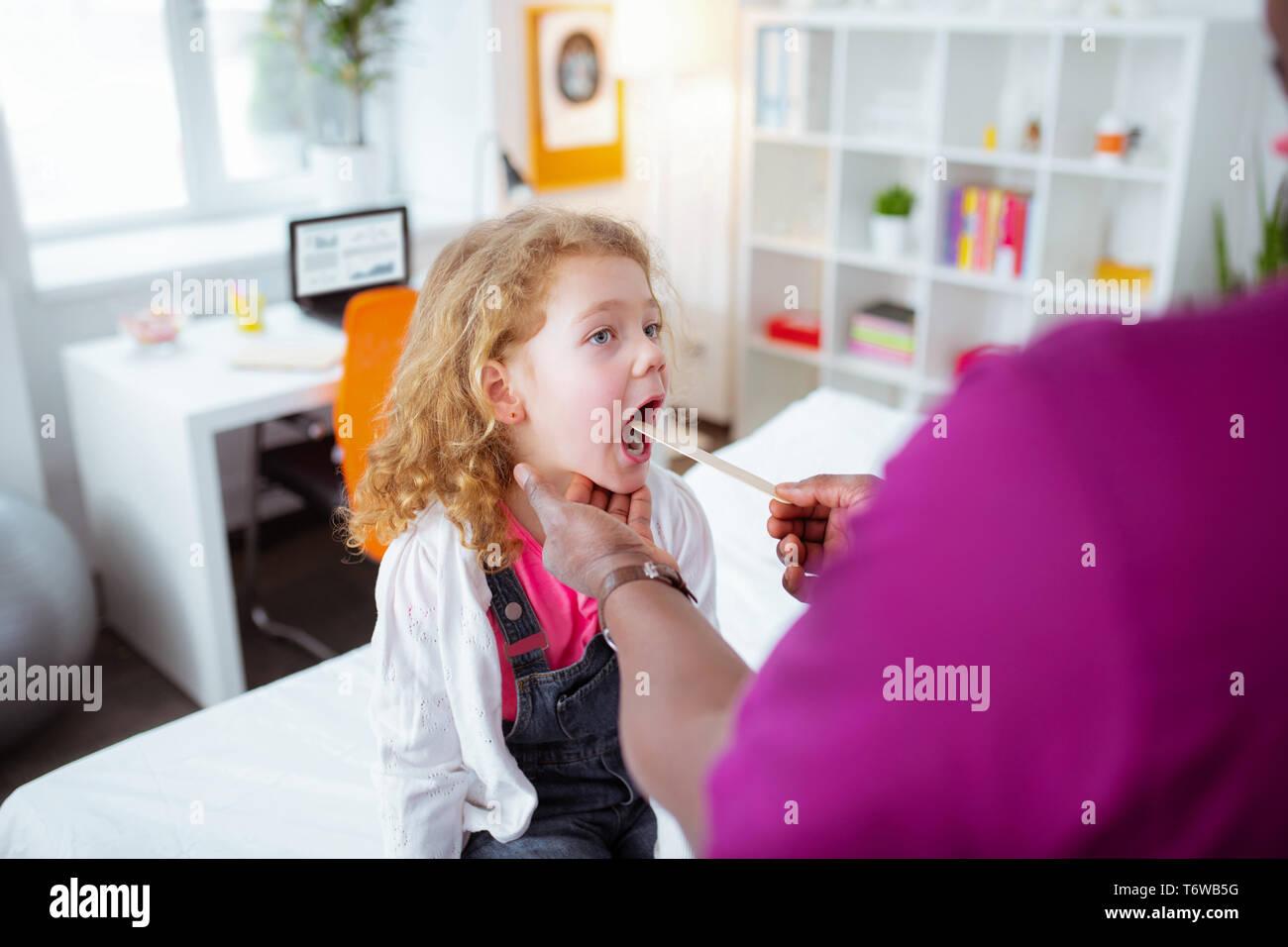 Cute curly girl Mund weit öffnen beim Besuch Arzt Stockbild