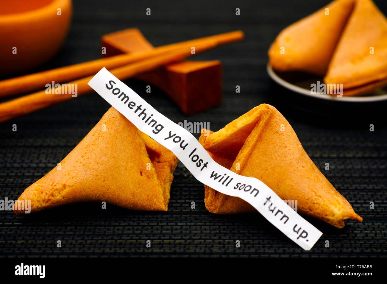 Streifen Papier mit dem Satz etwas, das Sie Bald drehen Sie verloren. von Fortune cookie, ein anderes Cookie und Essstäbchen auf Schwarz serviette Hintergrund. Stockbild