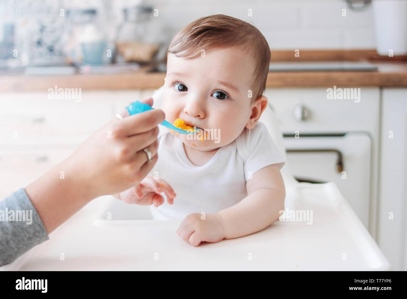 Charmantes kleines Baby Boy 6-8 Monate essen zunächst Essen Kürbis vom Löffel zu Hause Stockfoto