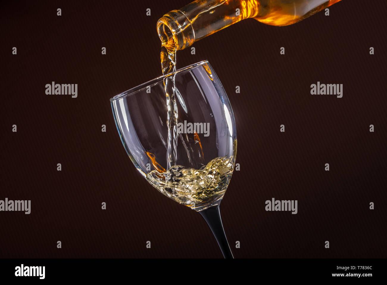 Weißwein gießen Glas auf braunem Hintergrund Stockfoto