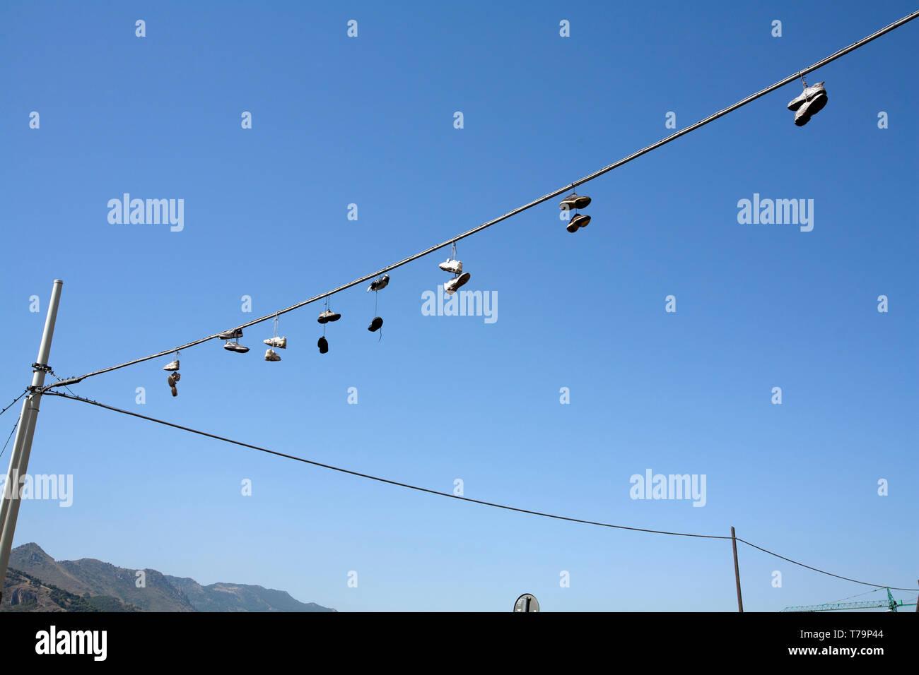 Schuhe hängen von Telefonleitungen als internationales