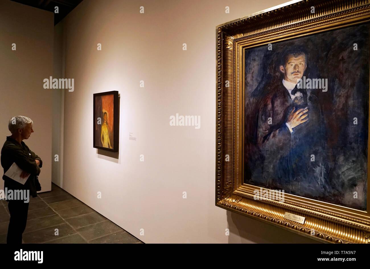 Ein Besucher vor Selbstporträt mit Zigarette (1895) von Edvard Munch in Sammlung von nasjonalmuseet für Kunst, Arkitektur og Design. Oslo, Norwegen Stockbild