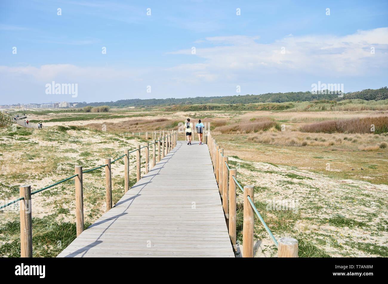 Paar auf Holz- zu Fuss über die Dünen in Portugal, in der Nähe des Strandes runing Stockfoto