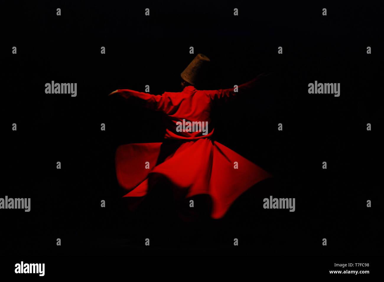 Wirbelnder Derwisch im roten Kleid auf schwarzem Hintergrund Stockfoto