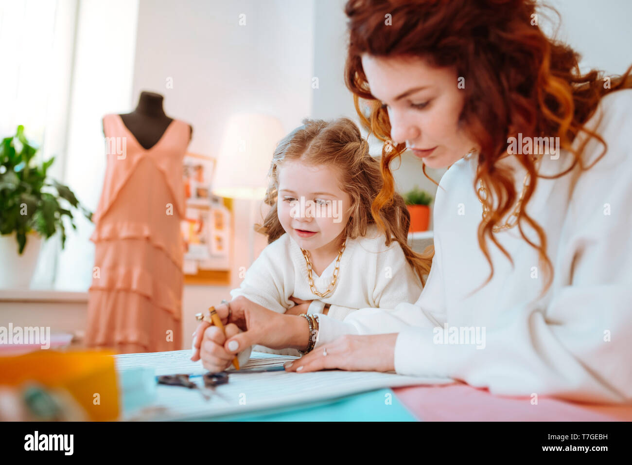 Ansprechende süße Mädchen stehen in der Nähe von Mutter entwerfen Kleider Stockbild