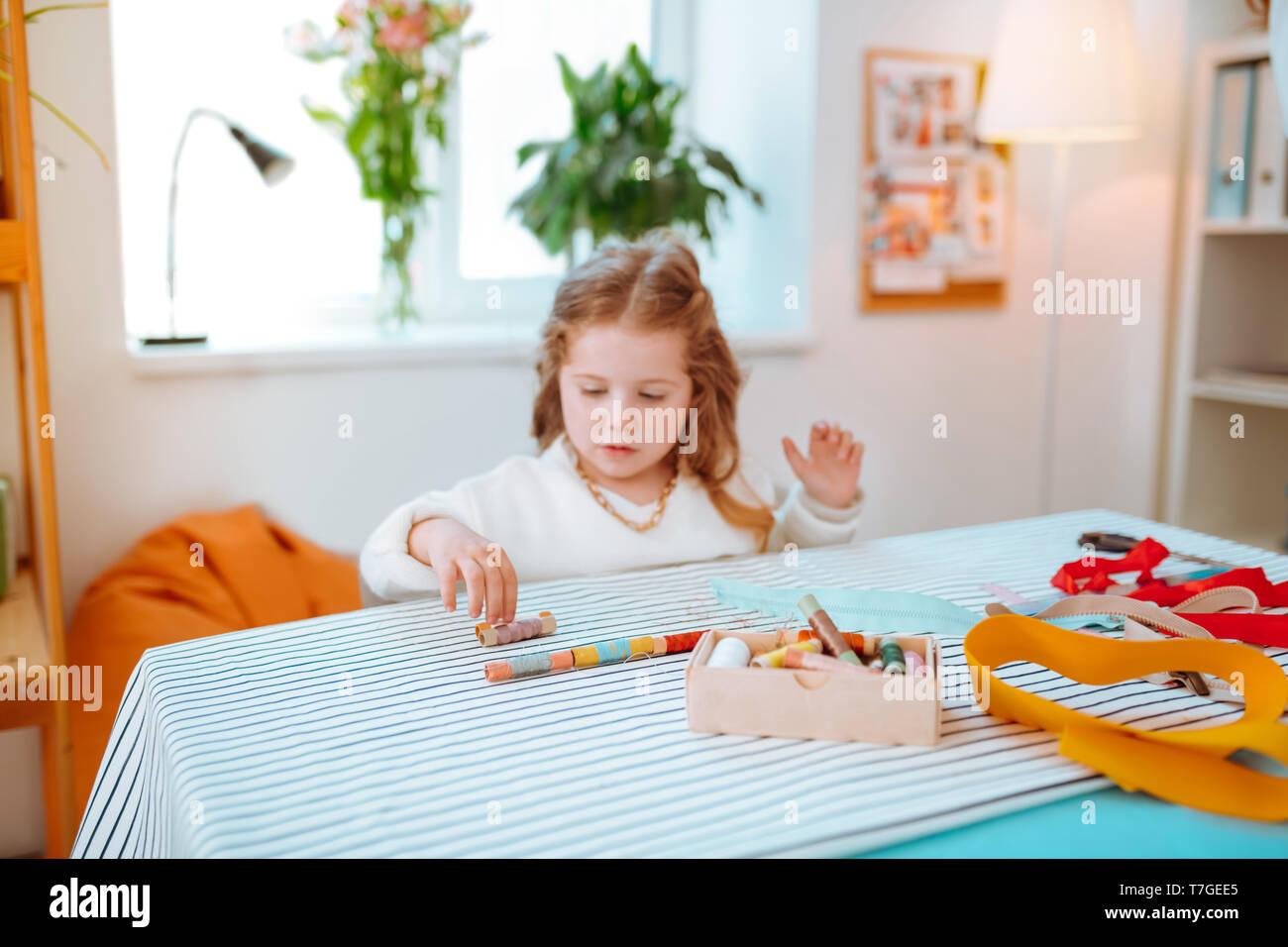 Lustig Mädchen spielen mit bunten Fäden mama Besuchen am Arbeitsplatz Stockbild
