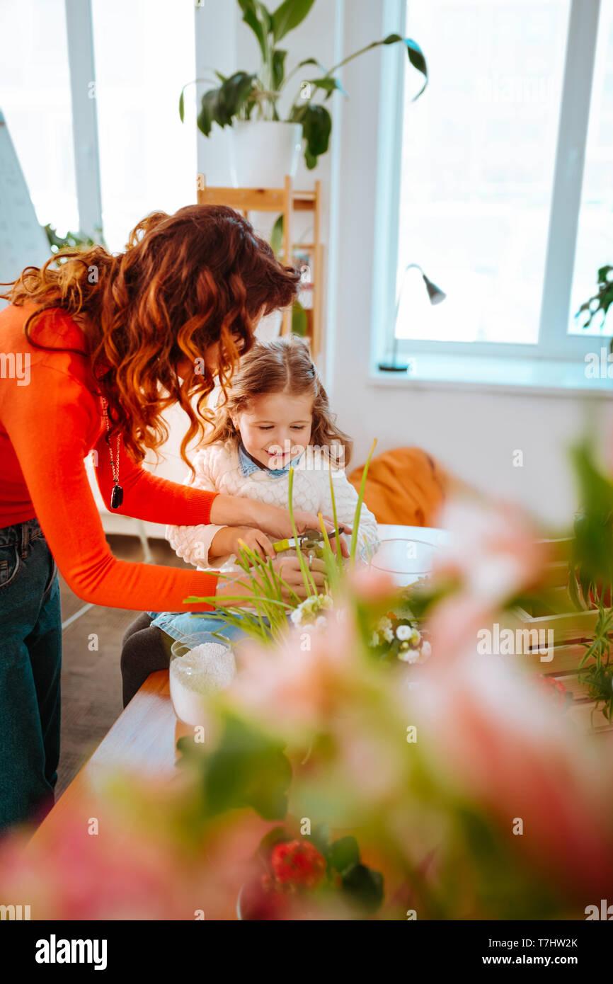 Mutter mit ihrer kleinen Tochter wie Pflege der Pflanzen zu nehmen Stockbild
