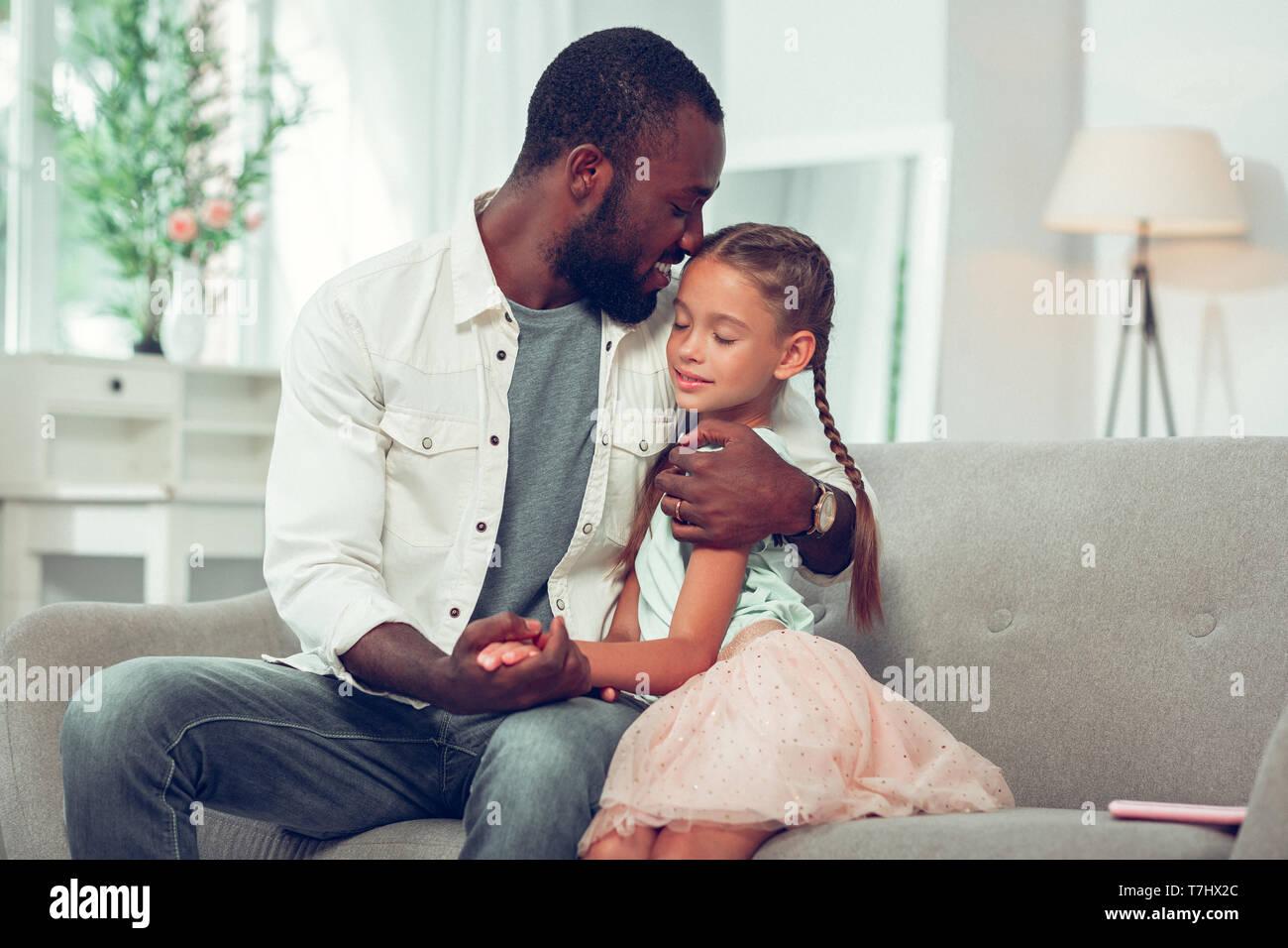 Liebevolle afroamerikanischen Vater zärtlich umarmen Schön hübsche kleine Tochter. Stockbild