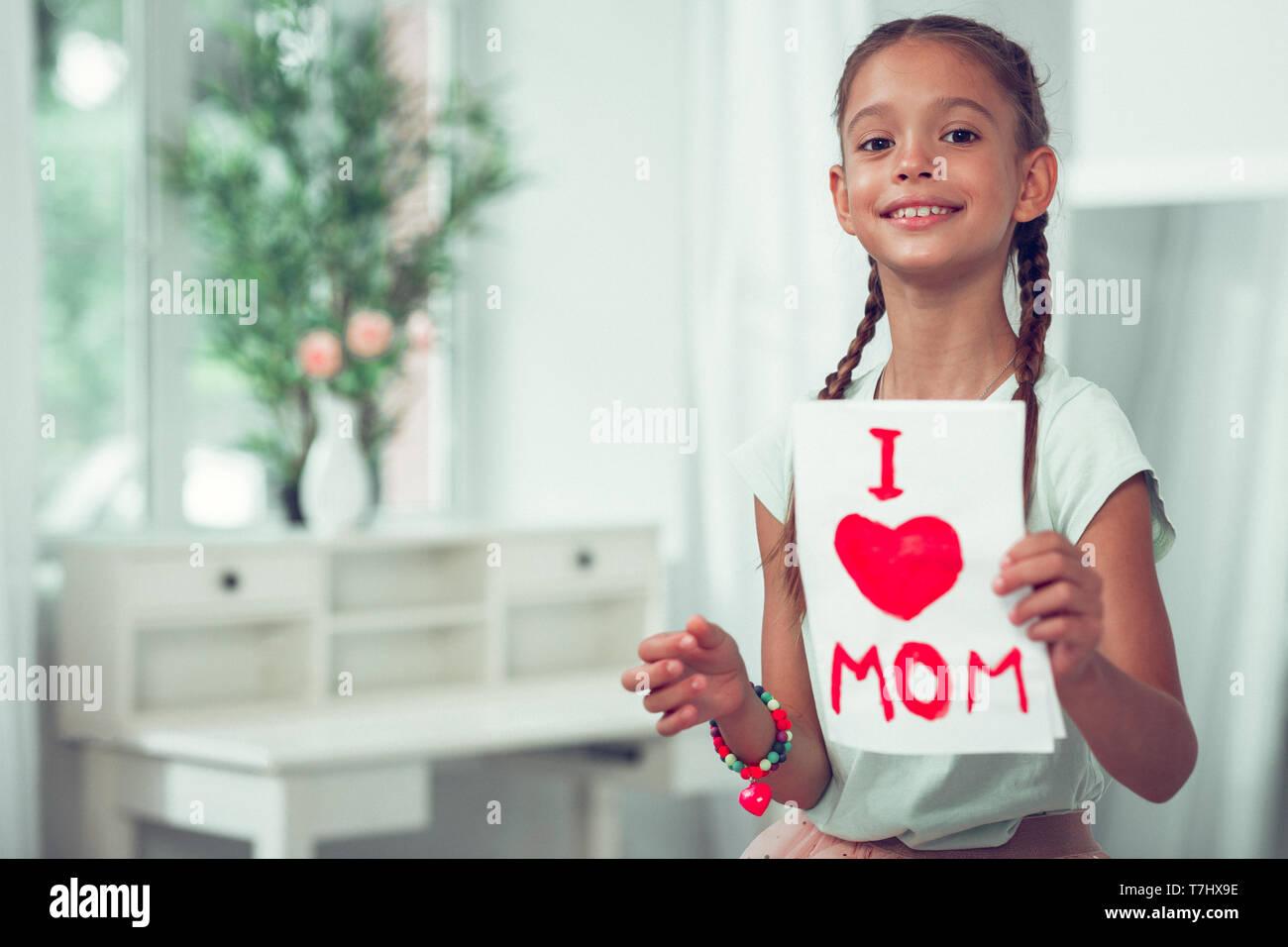 Strahlende Kind zeigt ein Gemälde mit ich Mom Zeichen der Liebe. Stockbild