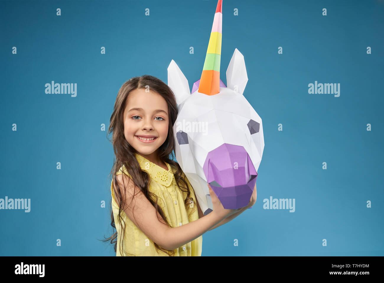 Portret der hübschen, kleinen, glücklichen Modell mit Papier Einhorn. Schöne positive Girl posiert, Kamera, und lächelnd die Hand auf weißen 3D Einhorn Kopf. Papercraft Konzept. Stockbild