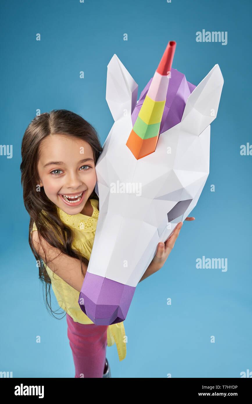 Kreative papercraft. Wunderschönes, kleines Modell mit weissen 3D Einhorn Kopf auf blauem Hintergrund posiert. Positive, süße Mädchen umarmt Papier Einhorn. Porträt eines Mädchens und Einhorn. Stockbild