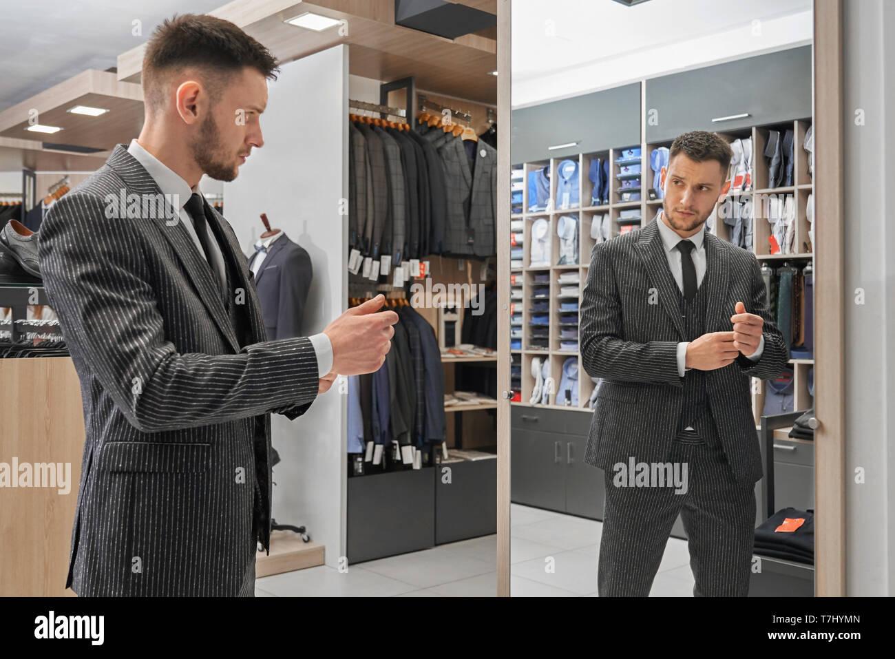 Schöner Mann im eleganten gestreiften Anzug stehen, zu Spiegel in Boutique und der Auswahl der Kleidung. Junge Kunden in modische Jacke, weißem Hemd und schwarzer Krawatte. Stockbild
