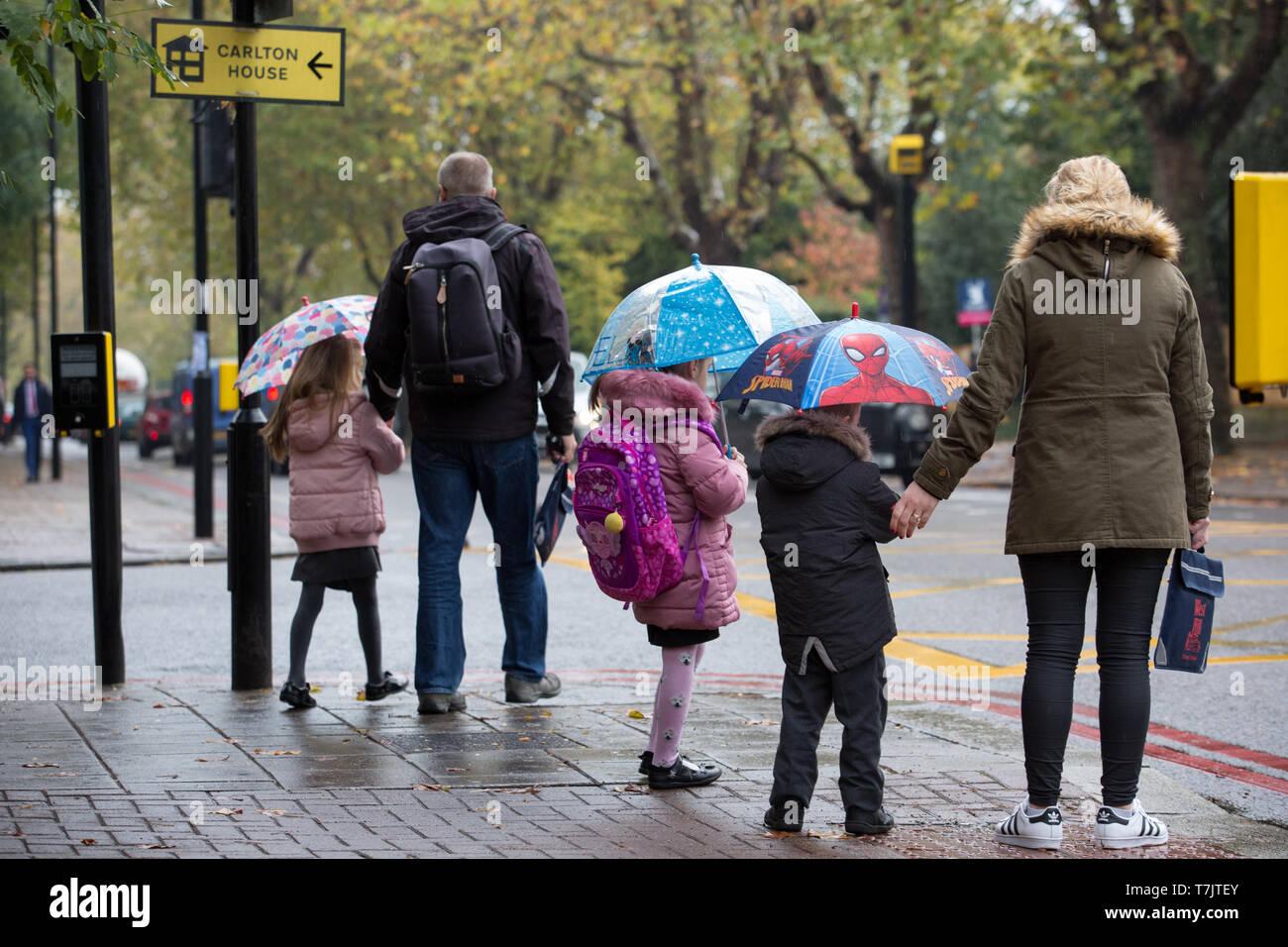 Kinder gehen mit ihren Eltern in den Regen halten Regenschirme in Wandsworth, London zur Schule Stockbild