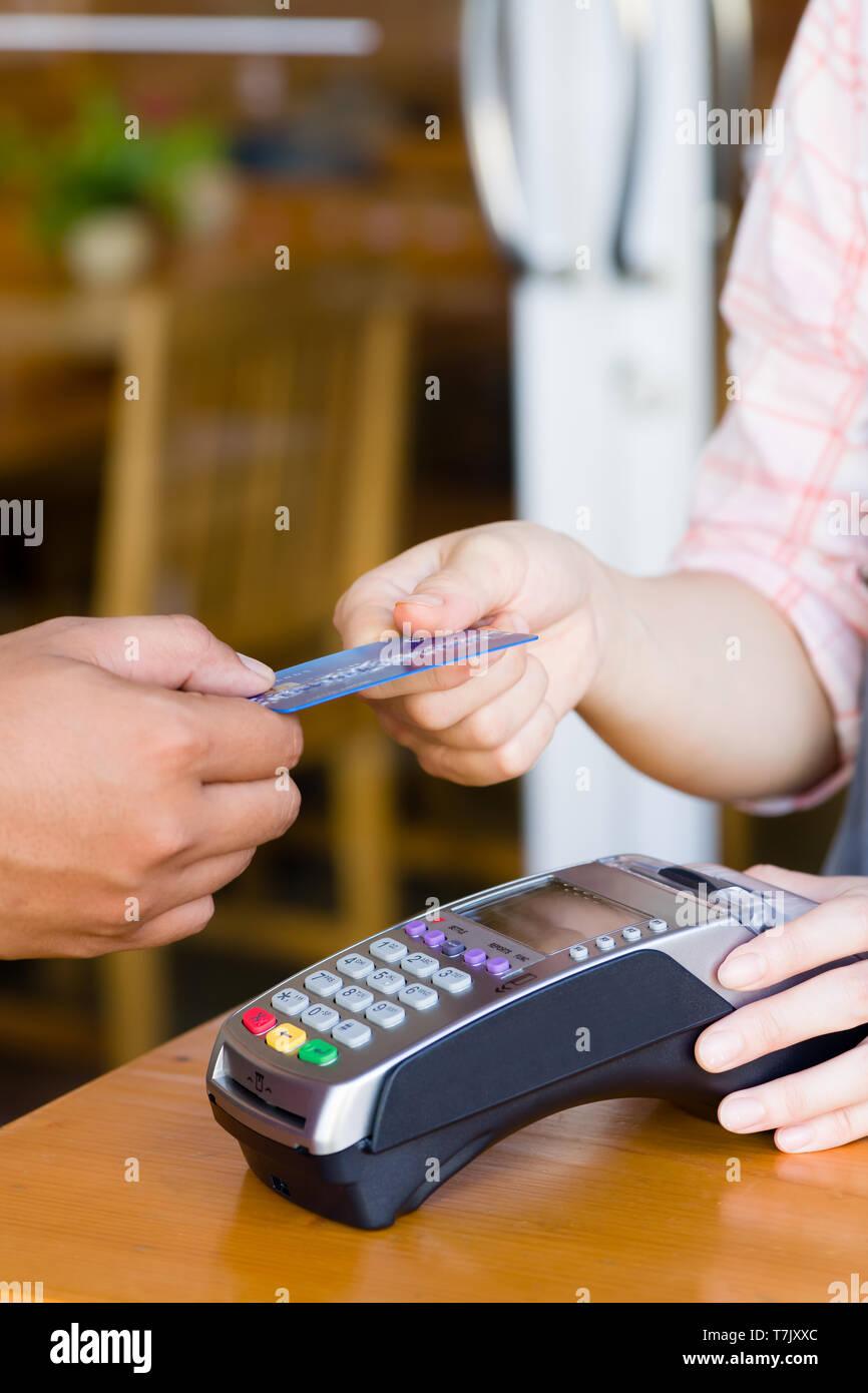 Kunden Hand Holding und die Zahlung für die Bestellung mit Kreditkarte im Cafe und Restaurant. Credit Card Payment Service. Kunde oder Kellner Eingeben von Code Stockfoto