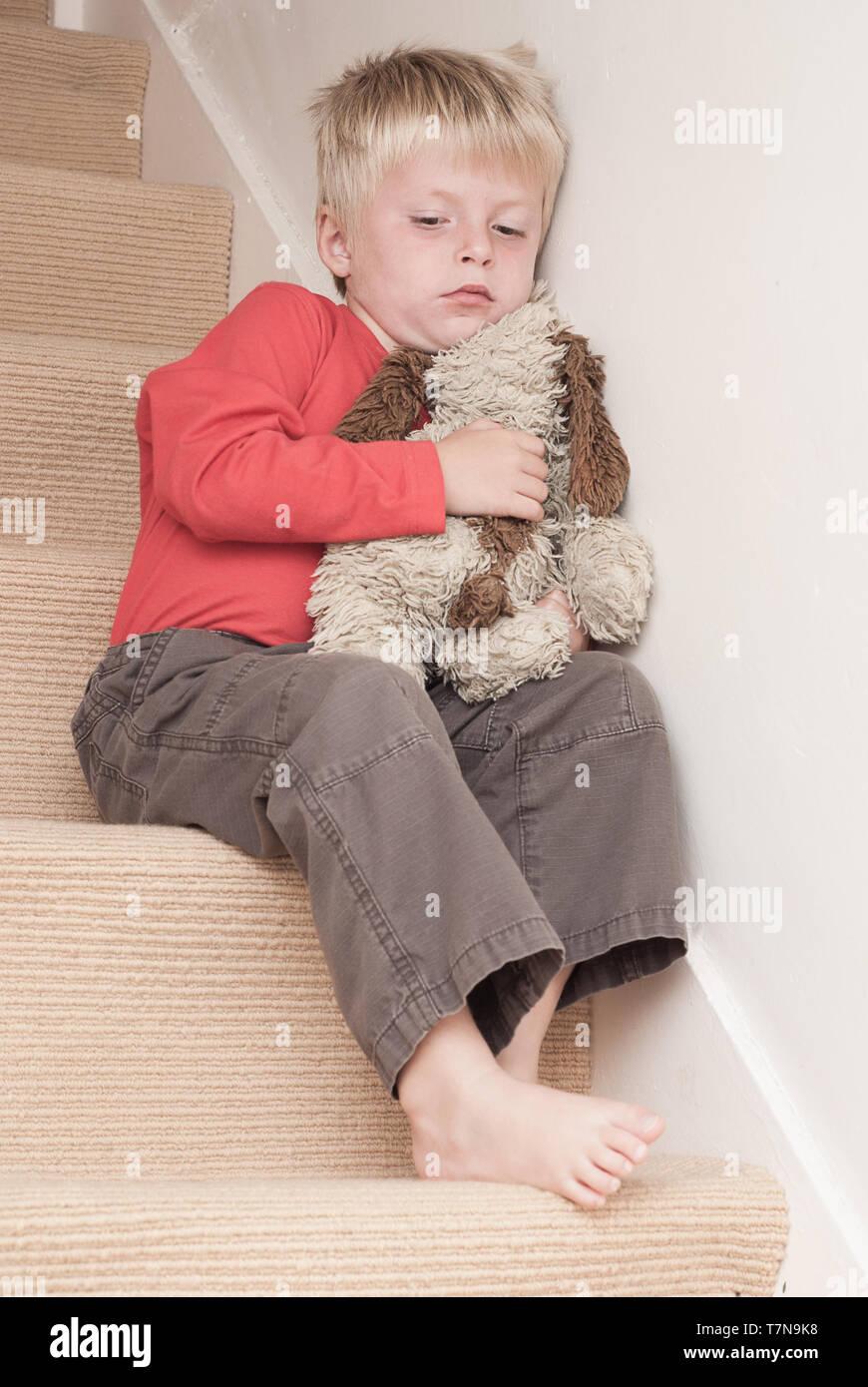 Einsame Kind sitzen auf der Treppe, sein weiches Spielzeug umarmt. Stockbild