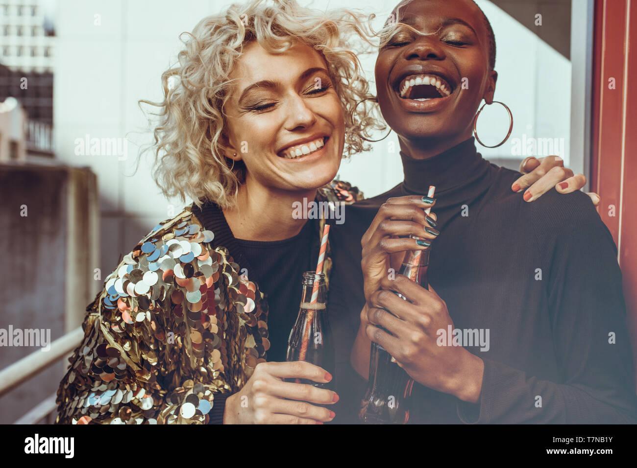 Multi-ethnischen Frauen Freunde zusammen mit Cola und Lachen. Zwei junge weibliche Freunde heraus hängen auf ihr Wochenende. Stockfoto
