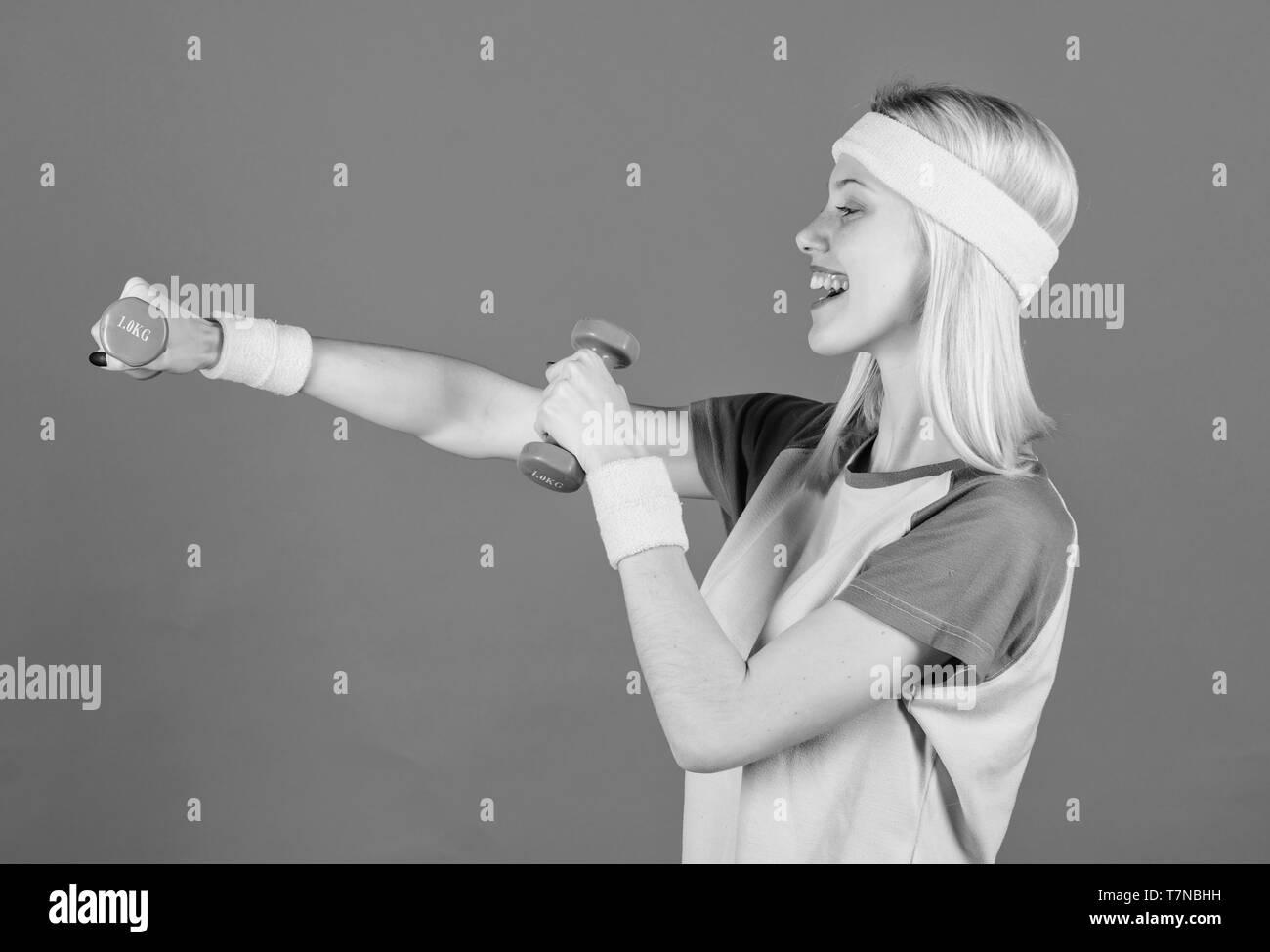 Fitness Concept. Mädchen trainieren mit Hantel. Training mit Kurzhanteln. Anfänger Hantel Übungen. Ultimative Oberkörpertraining für Frauen. Fitness Instructor halten wenig Hantel blauen Hintergrund. Stockbild