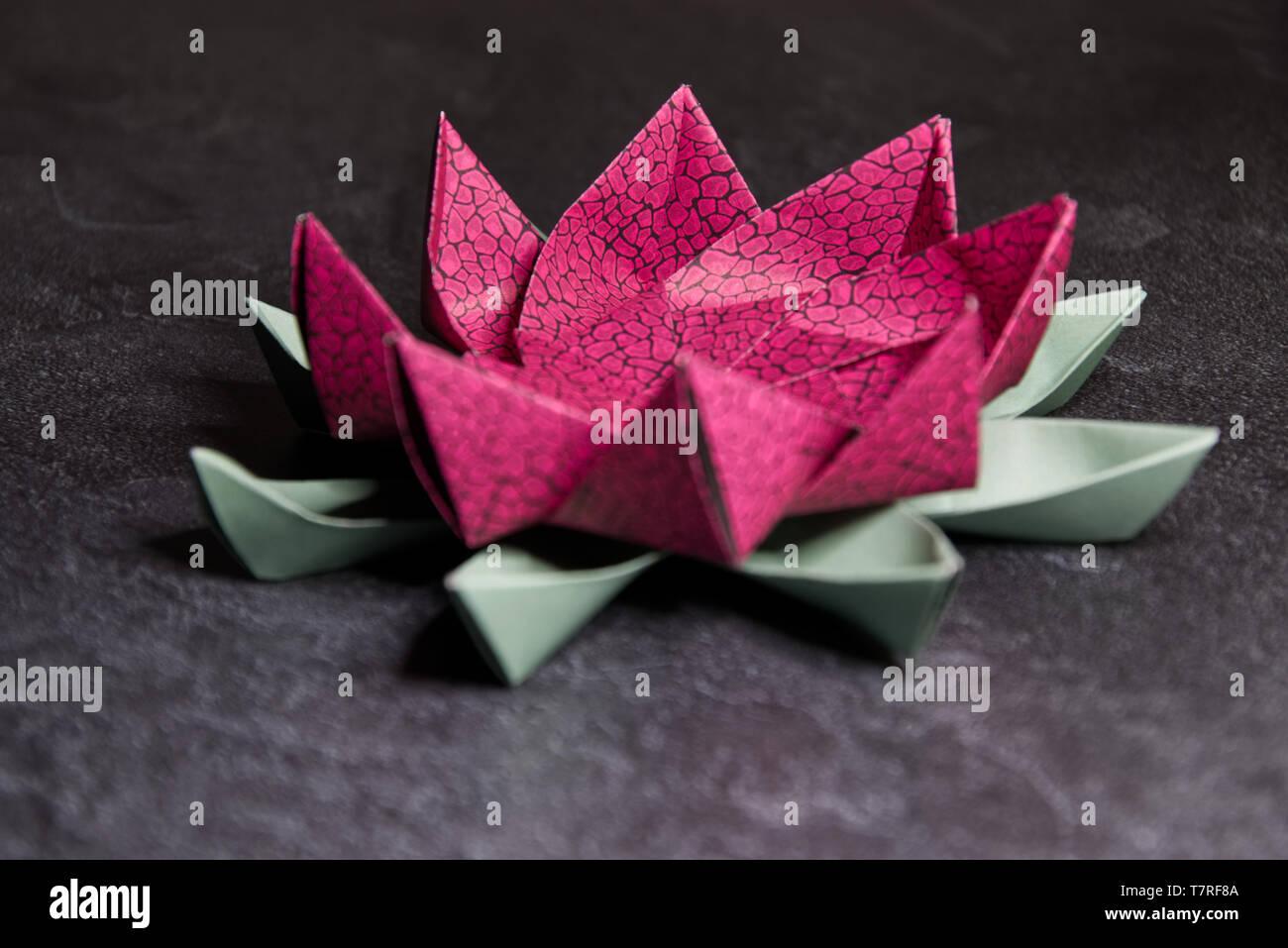 Rosa Origami Lotus Blume - Ars und Kunsthandwerk, Papier Kunst auf strukturierte Stein Backgrund Stockfoto