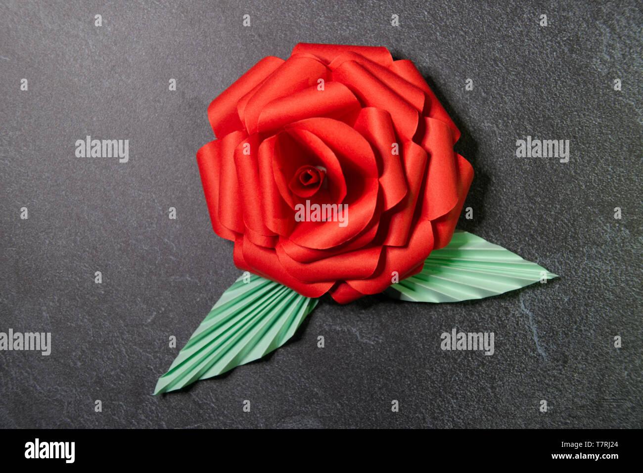 Red Origami Rosenblüte - Papier Kunst auf strukturierten Hintergrund Stockfoto