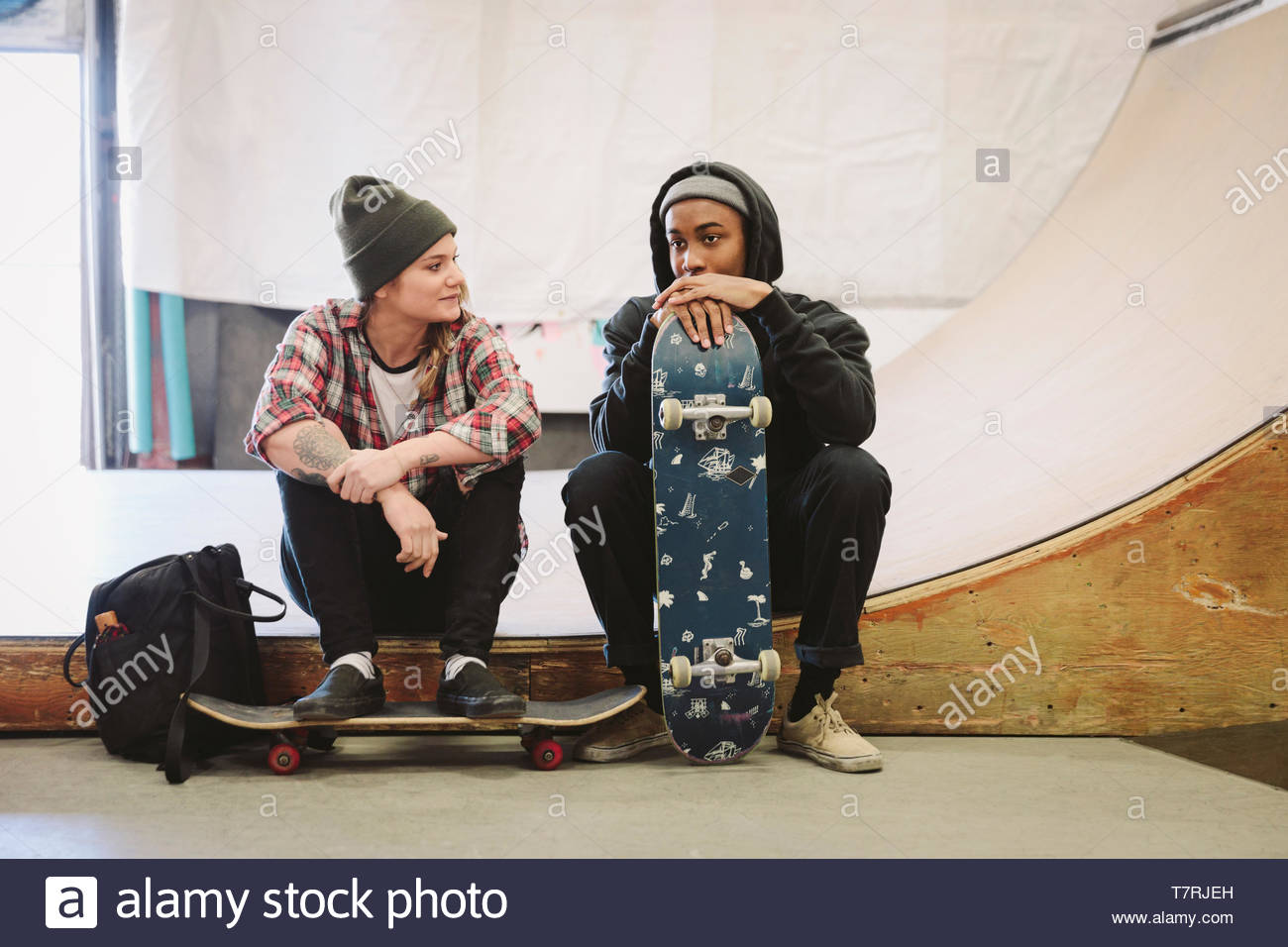 Junge Skateboarder reden indoor Skatepark Stockbild