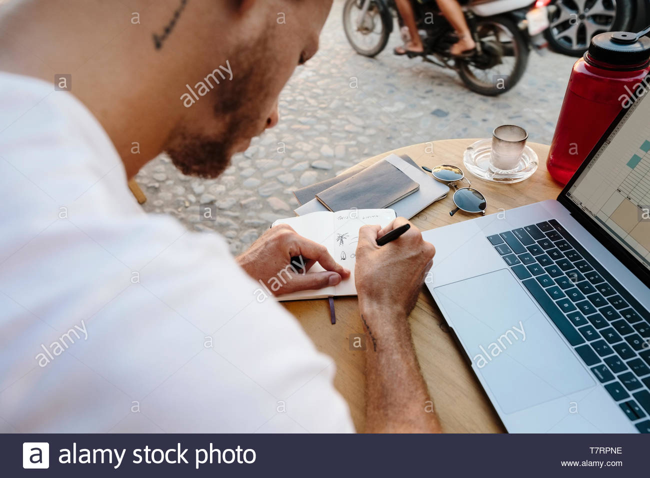 Junge männliche Touristen Sidewalk Cafe arbeiten, schreiben im Notebook Stockfoto