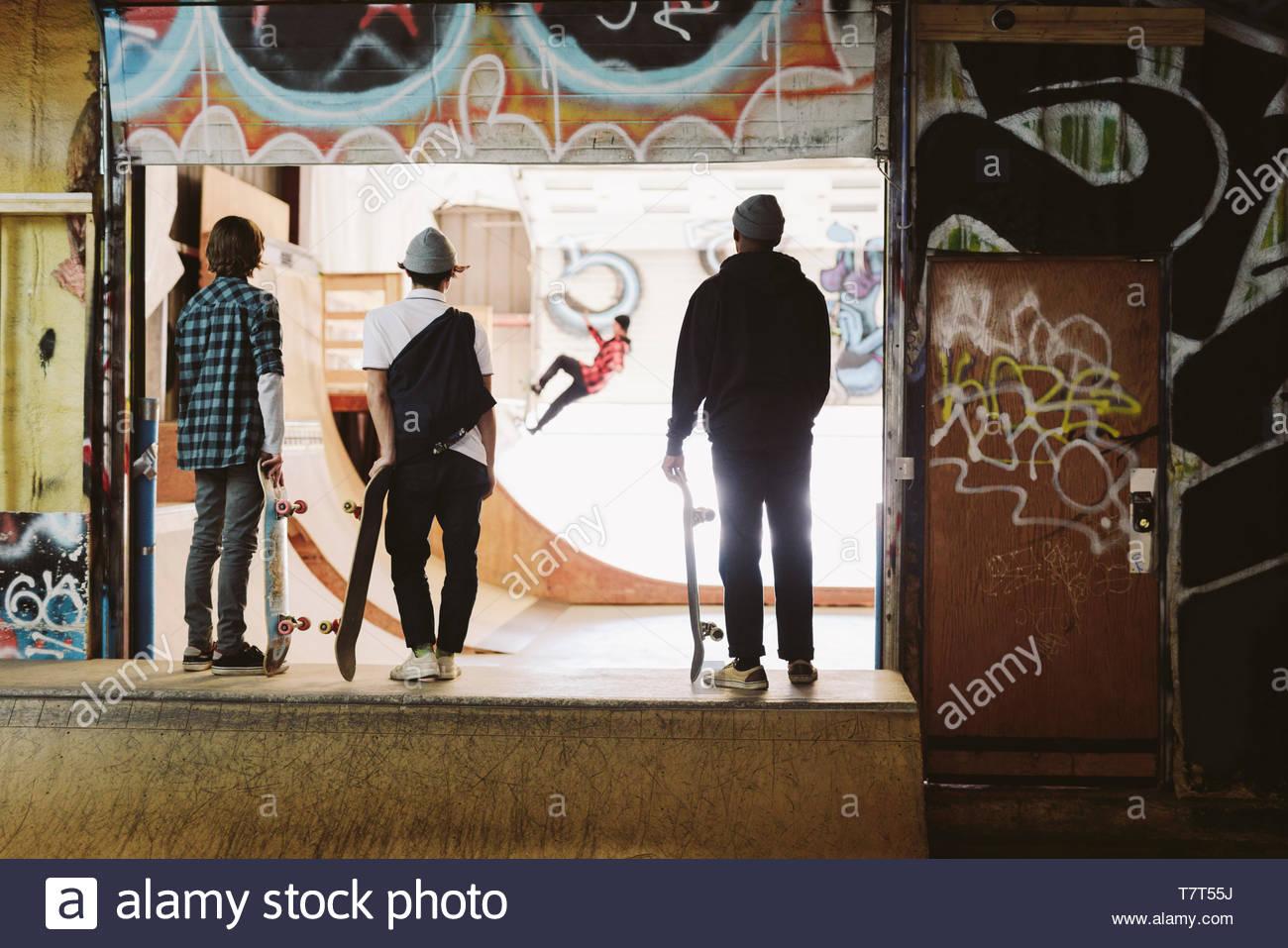 Jugendlichen Boarder beobachten Freund auf Rampe bei indoor Skatepark Stockbild