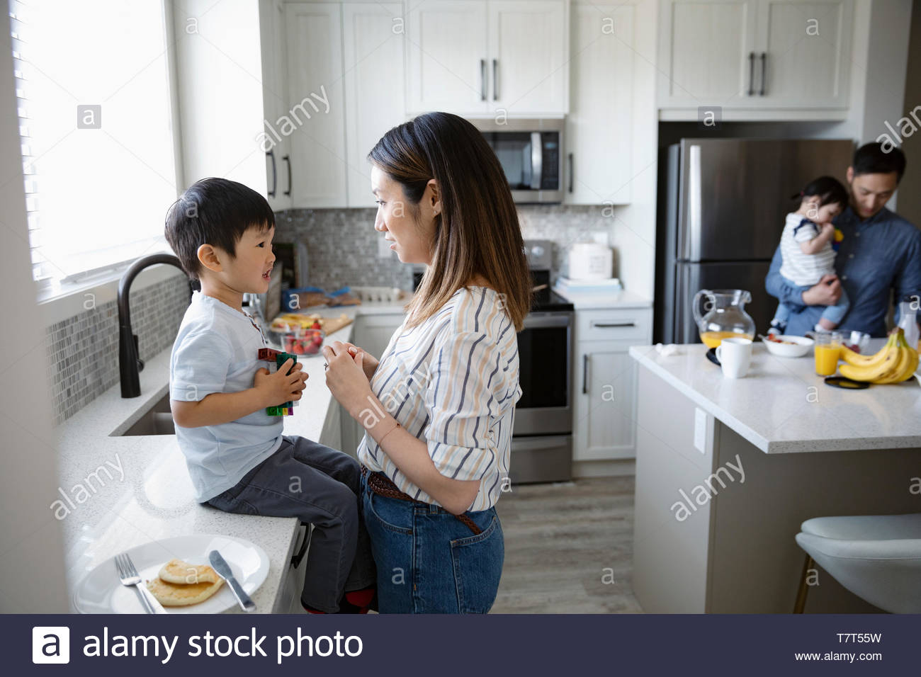 Mutter und Sohn sprechen in der Küche Stockbild