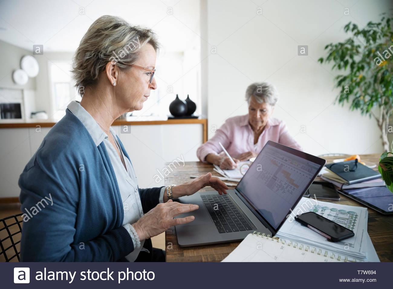 Frau Zahlung Rechnungen online at laptop während älterer Mutter Farben im Hintergrund Stockbild