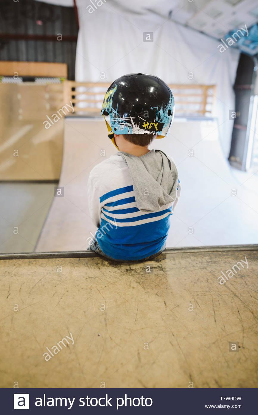 Junge sitzt oben auf der Rampe bei indoor Skatepark Stockbild