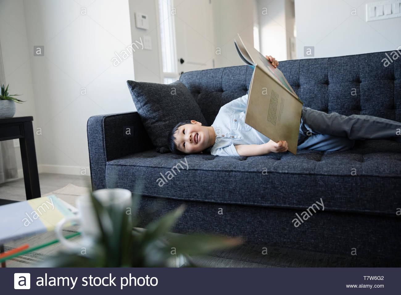 Cute boy lesen Buch auf dem Sofa im Wohnzimmer Stockbild
