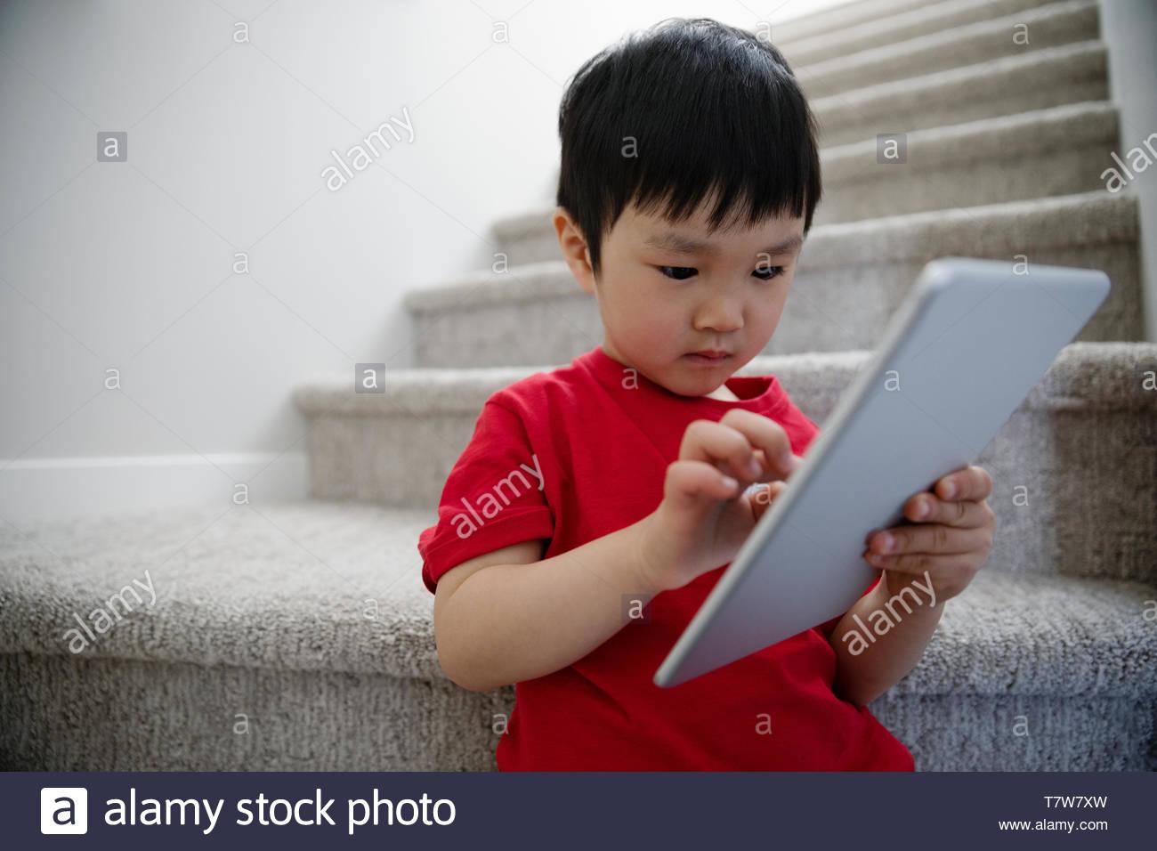 Cute Baby Boy mit digitalen Tablet auf Treppen Stockbild