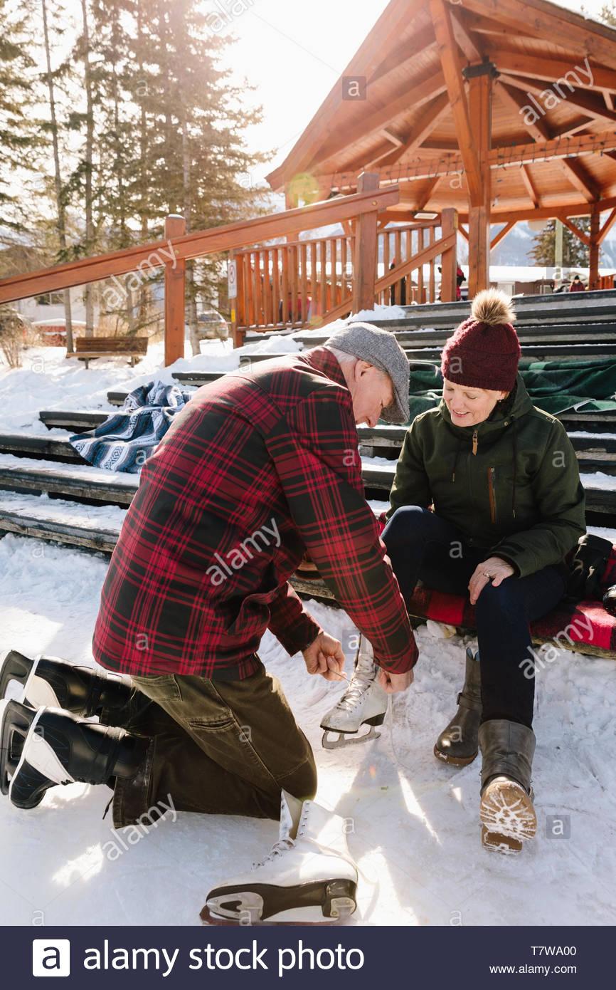 Ältere Menschen helfen Frau Riegel Schlittschuhe auf verschneiten Schritte Stockbild