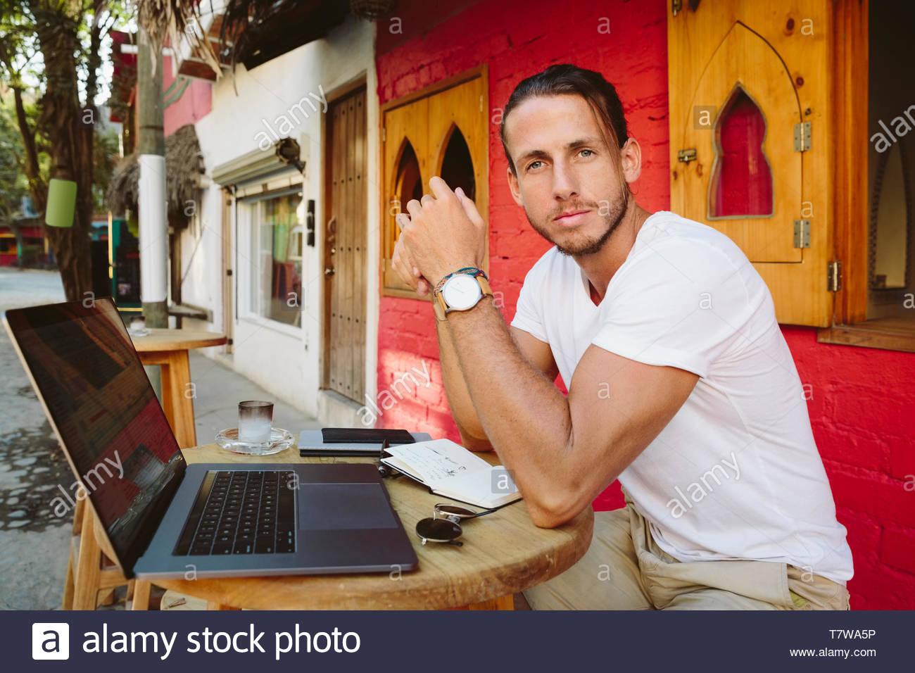 Portrait selbstbewussten jungen männlichen Touristen am Laptop zu Sidewalk Cafe arbeiten, Mexiko Stockbild
